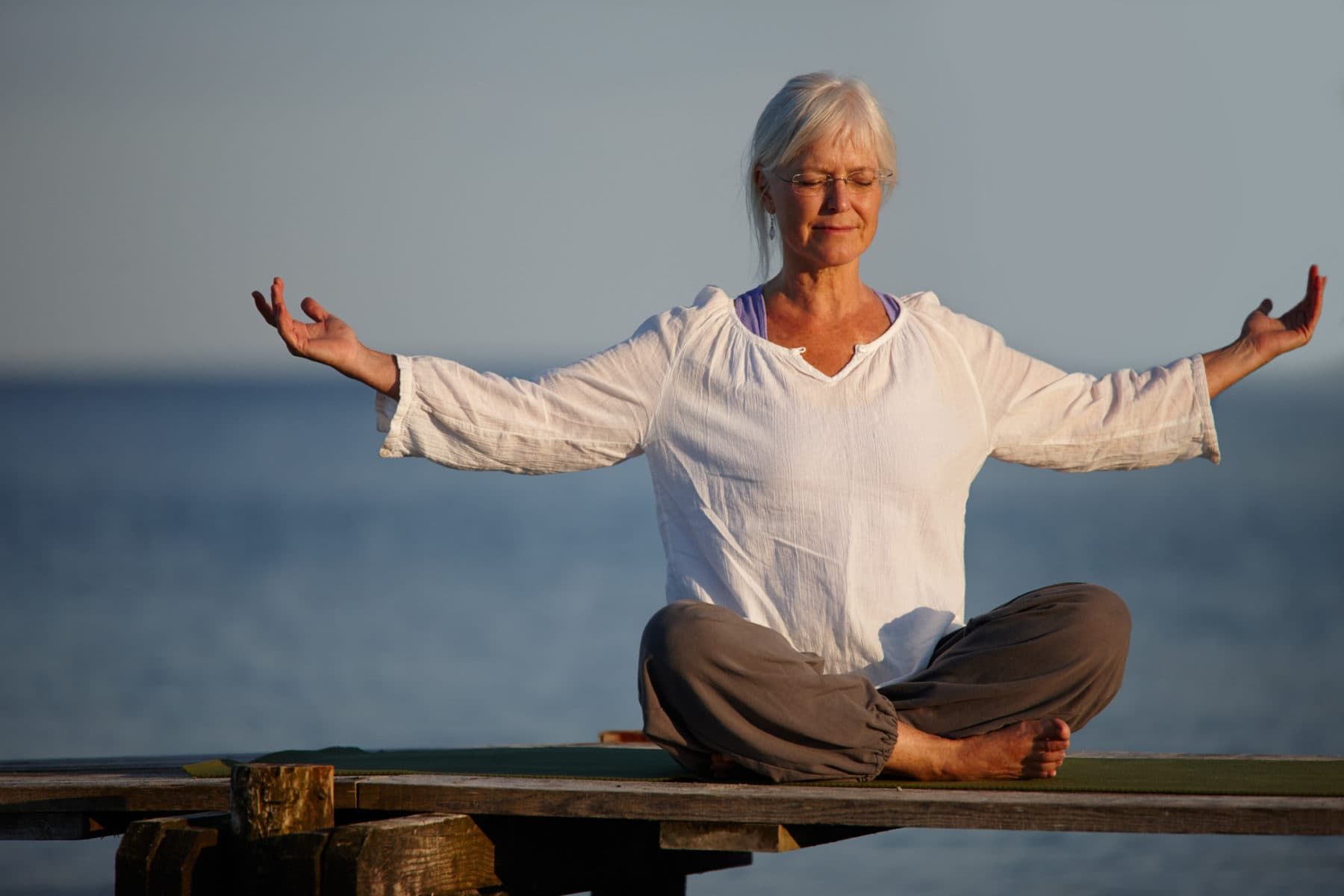 Full length shot of an attractive mature woman doing yoga on a pier out on the ocean