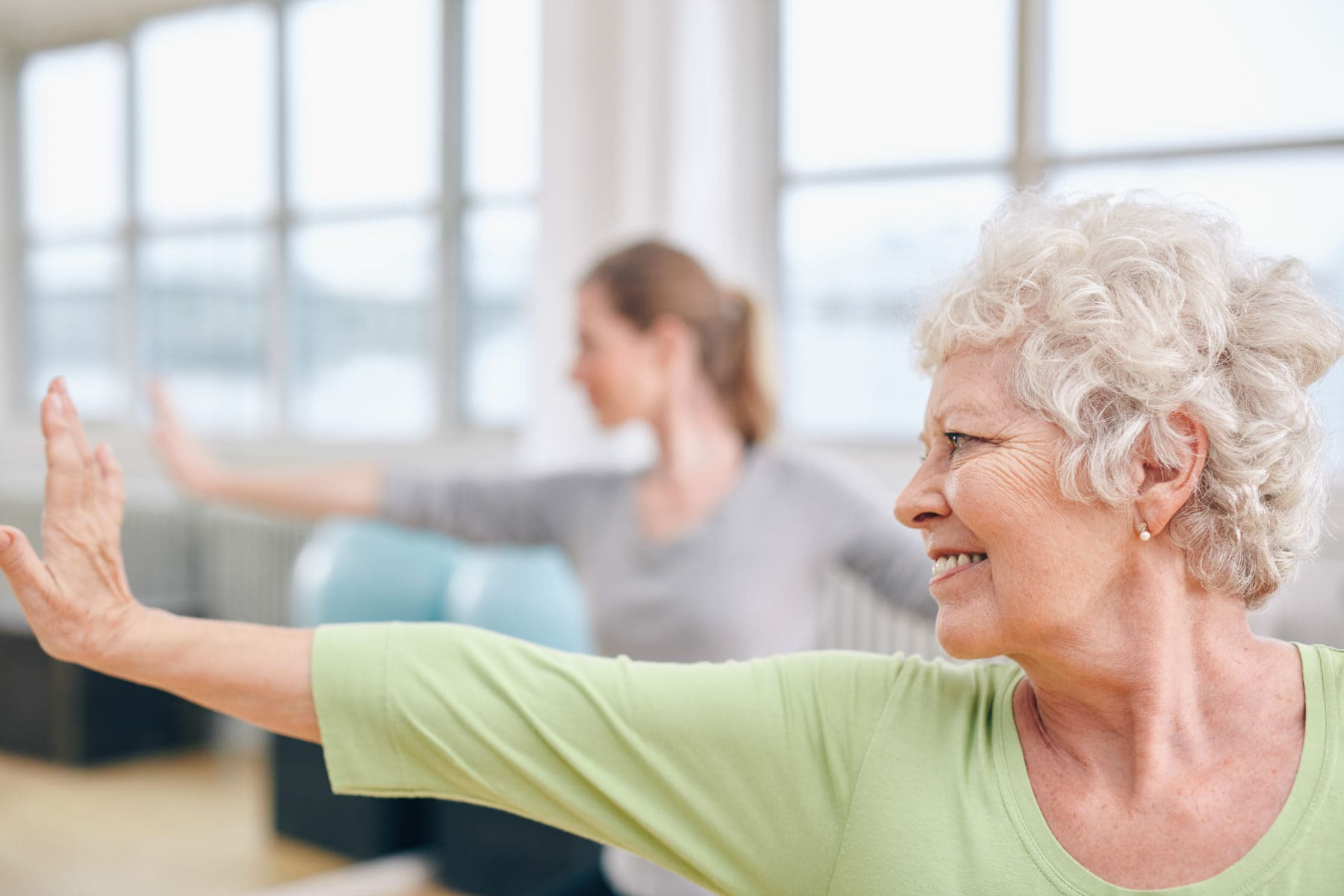 Close-up shot of elderly woman doing stretching workout at yoga class. Women practicing yoga at health club.