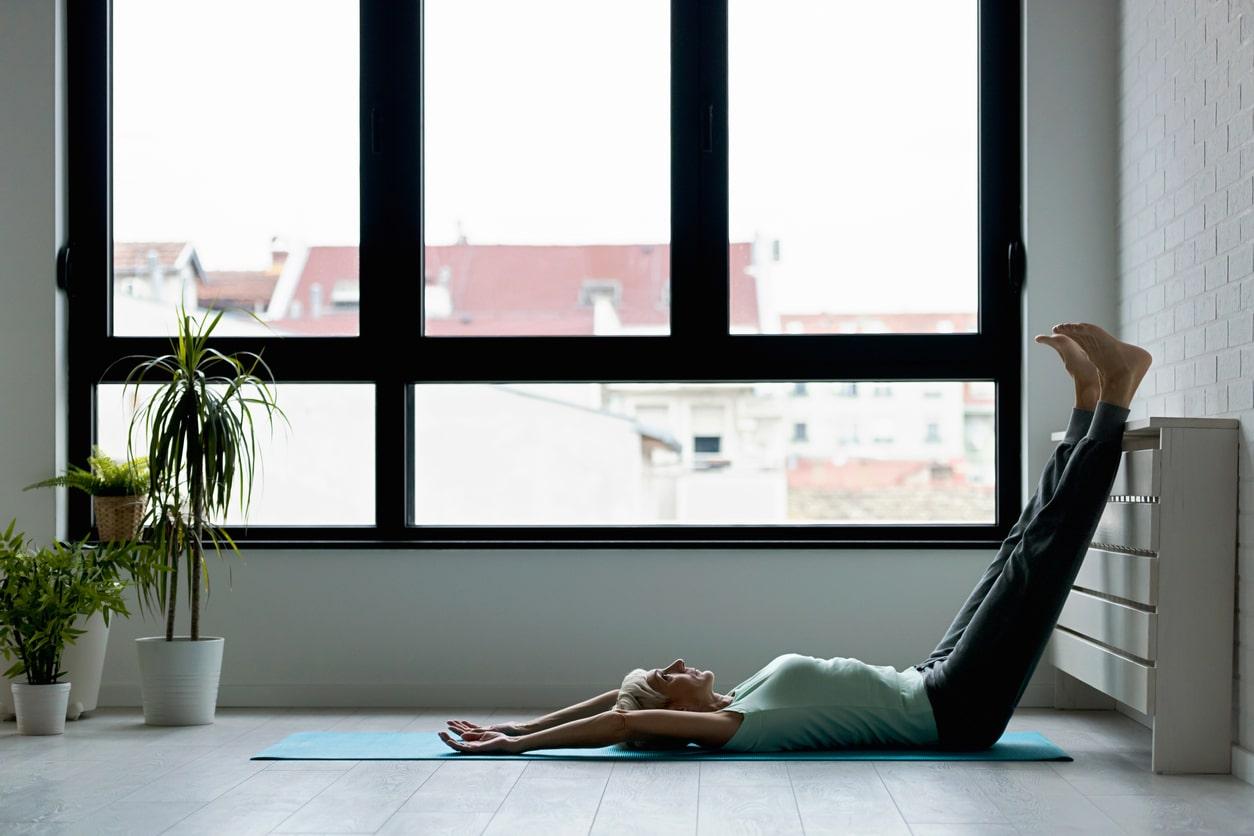 Active senior woman practicing yoga indoors. Yoga classes for seniors